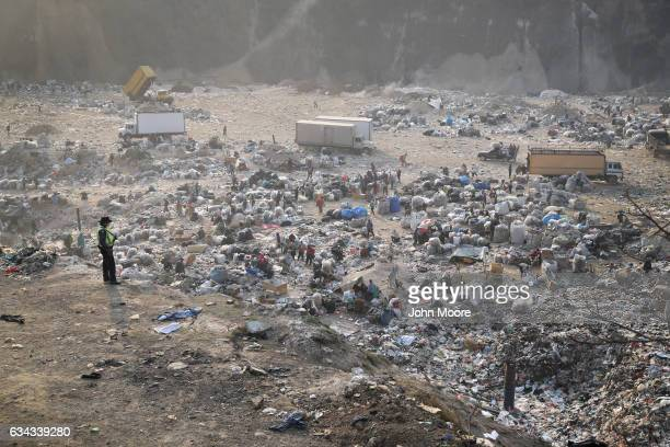 A policeman stands guard as garbage pickers work in the city's main landfill on February 9 2017 in Guatemala City Guatemala Grinding poverty and...