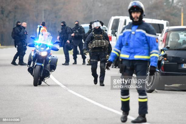 A policeman stands guard as gendarmes members of the French National Gendarmerie Intervention Group prepare on December 2 2017 in Auros western...