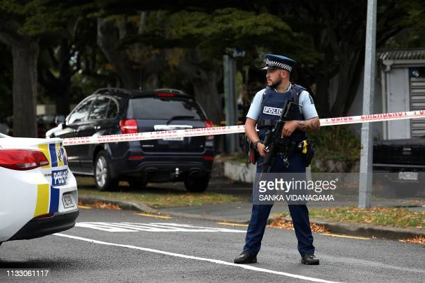 A policeman stands guard as others investigate a vehicle at the scene where a man died of stab wounds in Christchurch on March 27 2019 Christchurch...