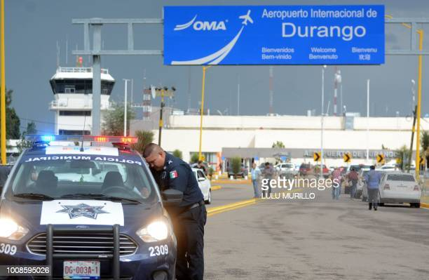 A policeman stands guard at the airport of Durango in northern Mexico after a plane carrying 97 passengers and four crew crashed during take off on...