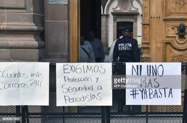 A policeman stands guard at the entrence of the government's palace during a demonstration to demand justice for slain Mexican photojournalist Edgar...