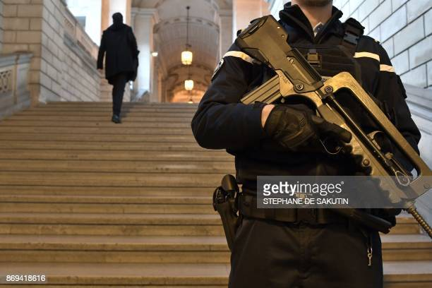 A policeman stands guard at the Paris courthouse on November 2 during the last day of the trial of Abdelkader Merah brother of Mohamed Merah a...