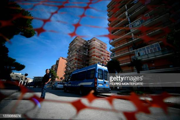 Policeman stands guard by a van of the State Police van on June 28, 2020 in Mondragone, north of Naples, within a block of flats where 43 positive...