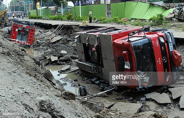 A policeman stands guard by damaged firetrucks after the gas explosions in the southern Taiwan city of Kaohsiung on August 1 2014 A series of...