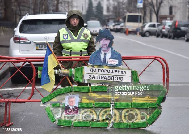 A policeman stands guard by the office of the Ukrainian President near a cardboard representing a tank bearing a portrait of Ukrainian President...