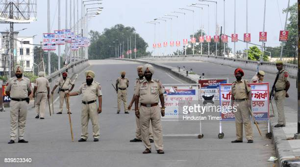 Policeman stands guard during the curfew on August 26 2017 in Patiala India At least 30 people were killed and over 250 injured in widespread...