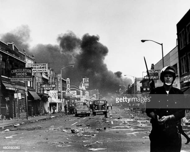 A policeman stands guard in a Detroit street on July 25 1967 as buildings are burning during riots that erupted in Detroit following a police...