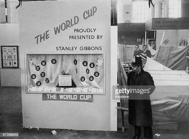 A policeman stands guard in Central Hall Westminster next to the stand at the National Stamp Exhibition where the Jules Rimet trophy was housed...