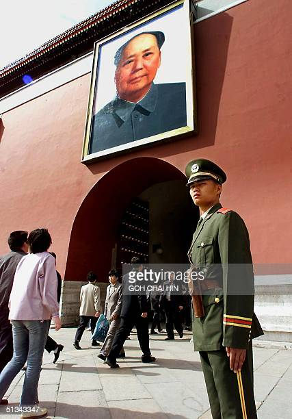 A policeman stands guard in front of the Tiananmen Gate with the portrait of Mao Zedong in Beijing 24 April 2001 as police tightened security around...
