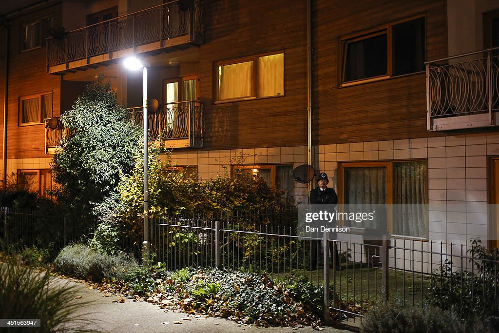 A Policeman stands guard in the garden of a block of flats in South London that are being investigated in connection with an alleged slavery case, on November 23, 2013 in London, England. Police are conducting house-to-house inquiries in the area after three women, of British, Irish and Malaysian descent, were allegedly held captive as slaves in an apartment in Brixton for thirty years.