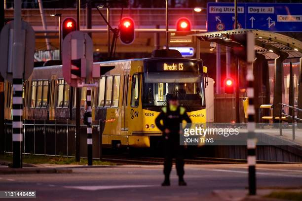 A policeman stands guard near a tram where a gunman opened fire killing at least three persons and wounding several in what officials said was a...