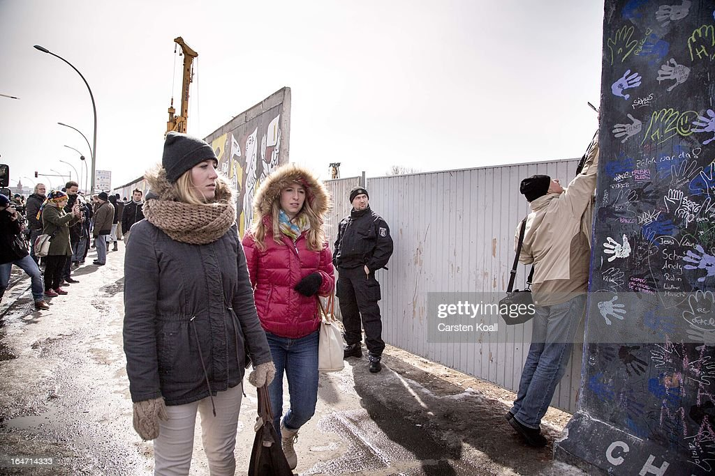 A policeman stands guard next to a section of the Berlin Wall which has been removed to make way for a luxury apartments development on March 27, 2013 in Berlin, Germany. Activists are seeking to stop a stretch of the Berlin Wall, known as the East Side Gallery, from being developed on by a real estate development company. A previous attempt by the developer to remove approximately 25 meters of the wall sparked protests that led to minor clashes with police. Negotiations had been underway and city officials had even offered the developer an alternative property, though removal continued today unannounced and to the surprise of opponents. The East Side Gallery is over one kilometer long and is among the city's biggest tourist attractions.