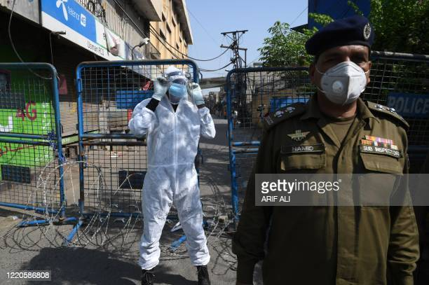 Policeman stands guard next to a street sealed by the authorities at a residential area in Lahore on June 17, 2020 after the COVID-19 coronavirus...