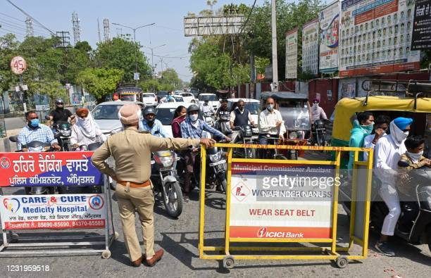Policeman stands guard next to barricades as the road was blocked after the state government's order to observe one-hour silence in honour of those...