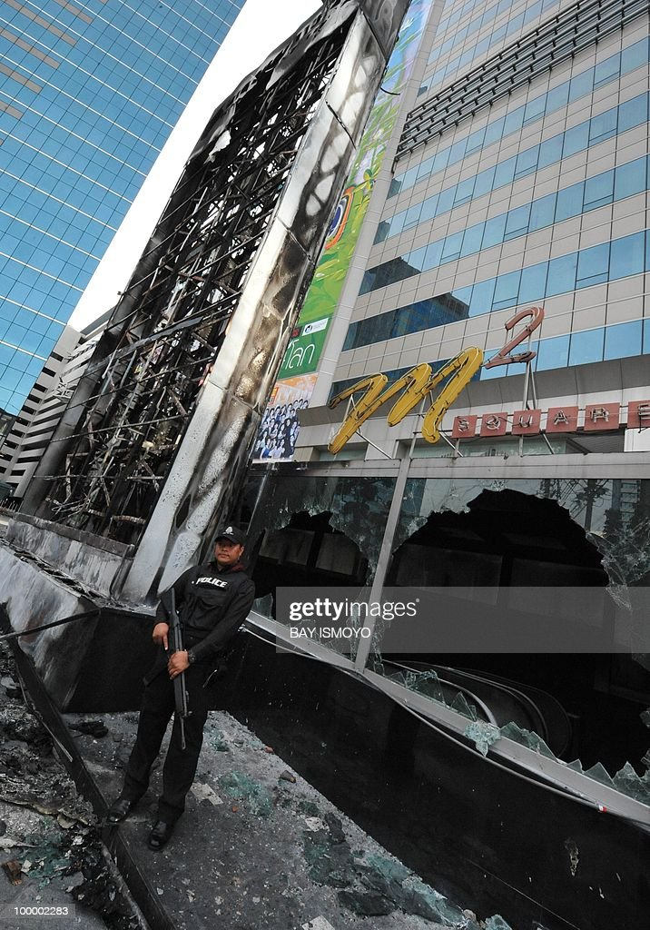 A policeman stands guard next to the burnt building of Thailand TV3 television station on Rama IV boulevard in downtown Bangkok on May 20, 2010. Plumes of smoke hung overhead as Bangkok emerged from an curfew aimed at quelling mayhem unleashed by enraged anti-government protesters targeted in an army offensive on May 2010.