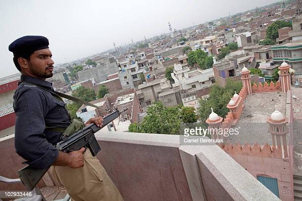 A policeman stands guard on the turret of the Garhi Shahu mosque as members of the persecuted Ahmadiyya community gather for Friday prayers on July...
