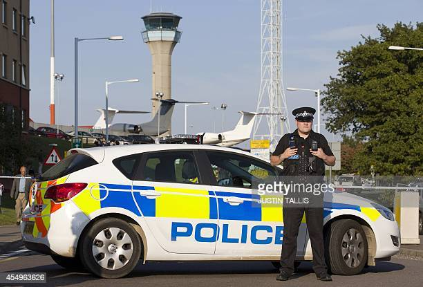 A policeman stands guard outside London Luton airport on September 8 following a security alert and an evacuation of the main terminal building...