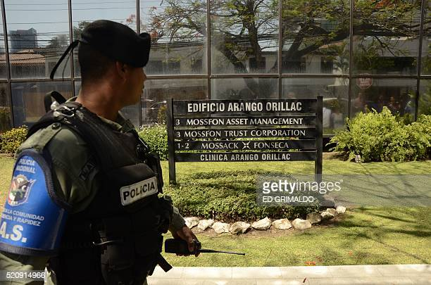 TOPSHOT A policeman stands guard outside Mossack Fonseca headquarters as members of the Construction Workers Union demonstrate at Panama city on...