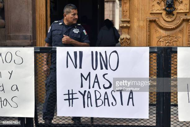 A policeman stands guard outside the government's palace during a demonstration to demand justice for slain Mexican photojournalist Edgar Daniel...