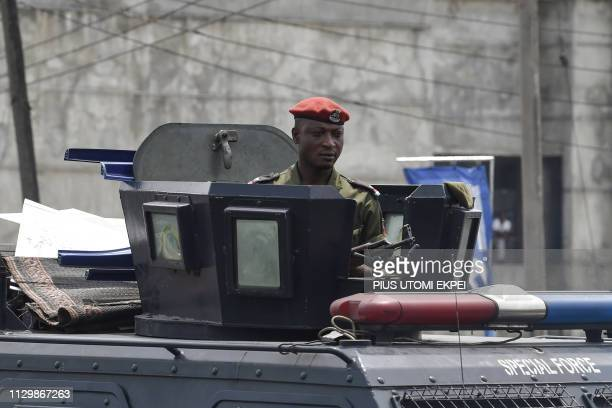 A policeman stands in an armoured Personel Carrier as protesters take part in a demonstration against the suspension of governorship elections in...