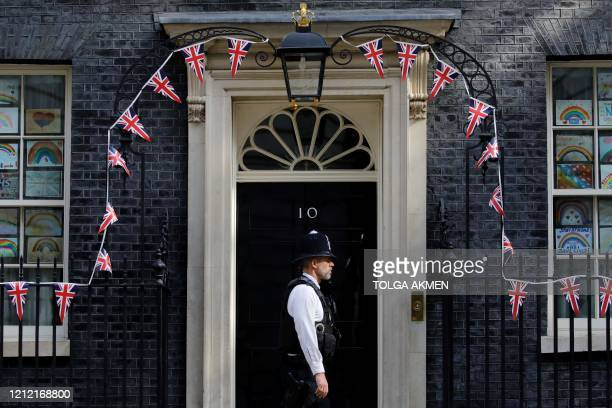 Policeman stands in front of 10 Downing street as bunting covers the facade to mark the 75th anniversary of VE Day May 8, 2020 in central London. -