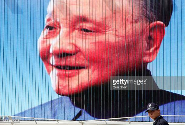 Policeman stands in front of a billboard featuring Deng Xiaoping, commonly recognized as the architect of China's economic reform, in Shanghai, China...