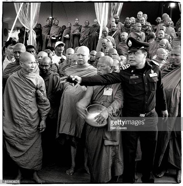 Policeman stands in front of a gathering of senior monks at a merit-making ceremony at Sanam Luang in Bangkok. More than 90% of the Thai population...