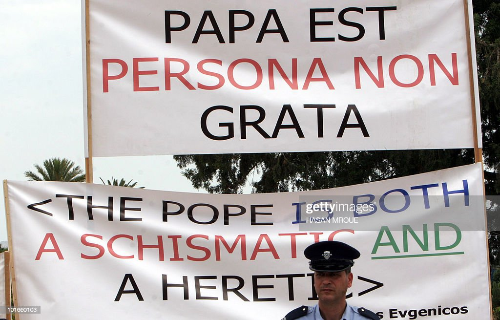 A policeman stands in front of anti-Pope banners during a demonstration by Greek Orthodox Cypriots to protest the visit of Pope Benedict XVI, outside the Eleftheria Sports Centre in Nicosia as the pontiff holds a mass inside on the third and final day of his visit to the mostly Greek Orthodox Mediterranean island of Cyprus on June 6, 2010.