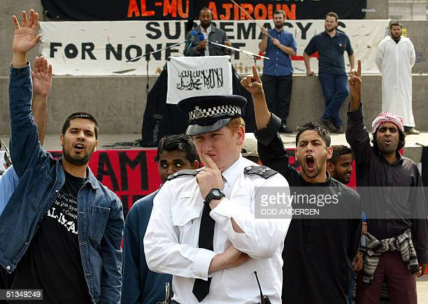 A policeman stands in front of devotees shouting 'Allah u Akhbar' during the 'Rally for Islam' at Trafalgar Square in central London 25 August 2002...