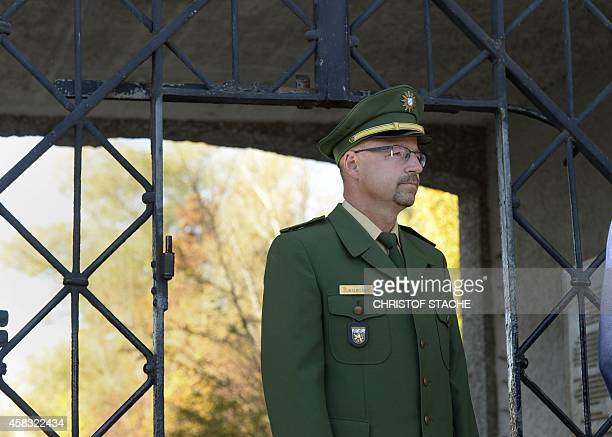 A policeman stands in front of the entrance gate without the door of the former Nazi concentration camp in Dachau southern Germany on November 3 2014...