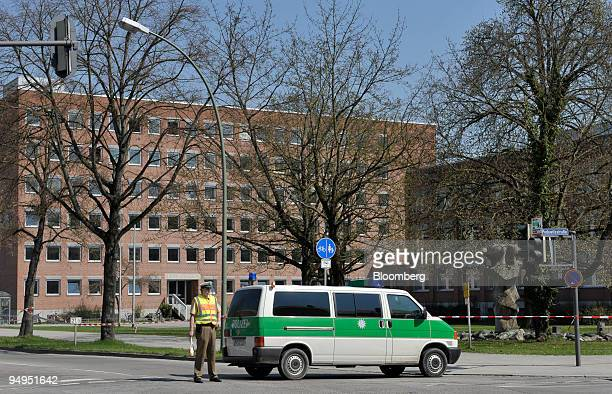 A policeman stands in front of the regional court site of a shooting in Landshut Germany on Tuesday April 7 2009 A 60yearold gunman opened fire in a...