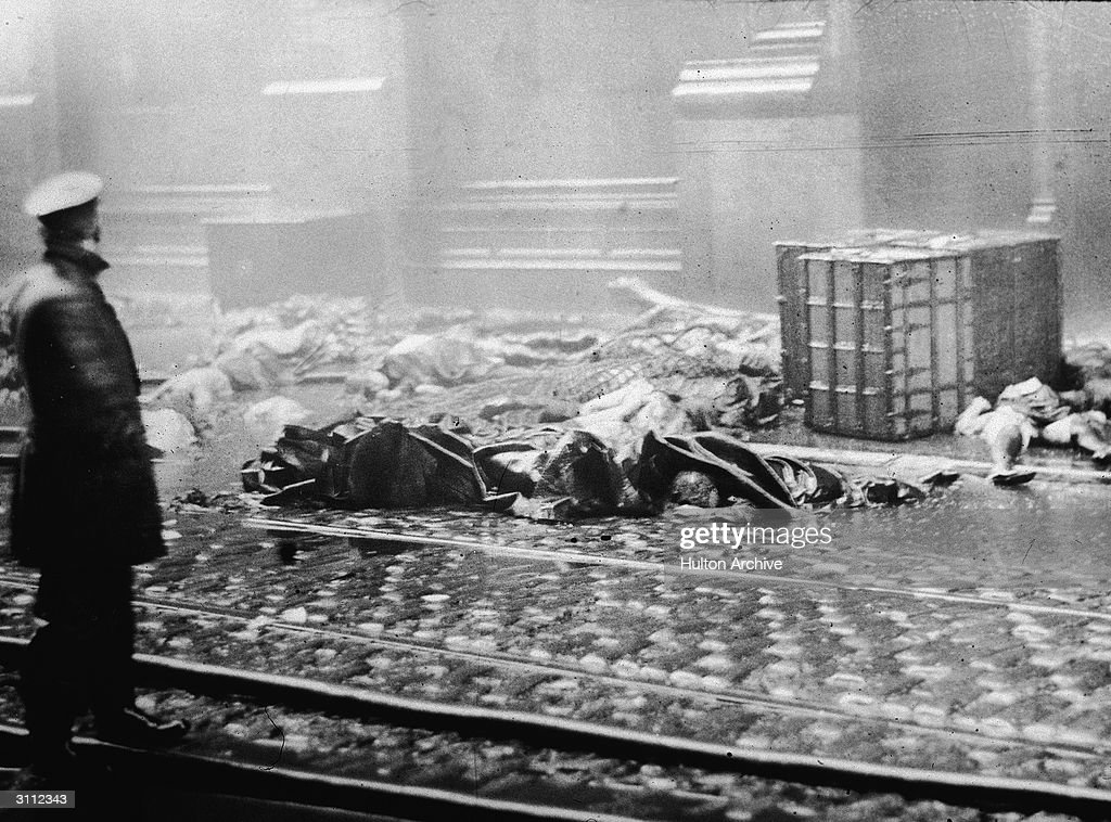 A policeman stands in the street, observing charred rubble and corpses of workers following the Triangle Shirtwaist Company fire in New York City, March 25, 1911.