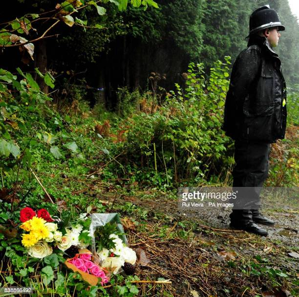 A policeman stands near flowers outside woodland near the village of Aberkenfig Bridgend south Wales where the body of Rebecca Aylward was found on...