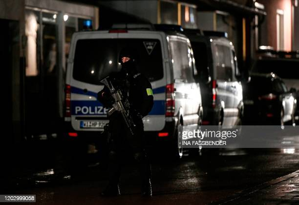 A policeman stands near the house of a driver who steered his car into a carnival procession February 24 2020 in Volkmarsen near Kassel central...