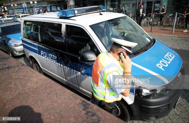 A policeman stands next to a police car that has been attacked with black color on July 7 2017 in Hamburg northern Germany where leaders of the...