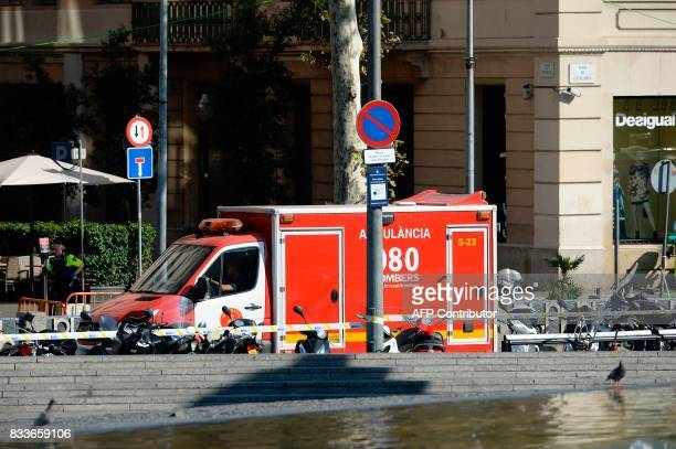 A policeman stands next to an ambulance after a van ploughed into the crowd injuring several persons on the Rambla in Barcelona on August 17 2017 /...