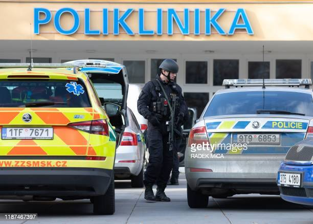 Policeman stands next to his vehicle in front of the Faculty Hospital in Ostrava, eastern Czech Republic, after a gunman opened fire, killing six...