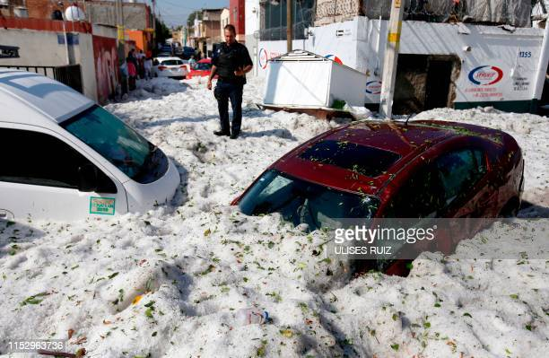 Policeman stands next to vehicles buried in hail in the eastern area of Guadalajara, Jalisco state, Mexico, on June 30, 2019. - The accumulation of...