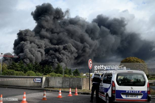 A policeman stands on a blocked road in Le PetitQuevilly on September 26 2019 as smoke billows from a Lubrizol factory classified Seveso...