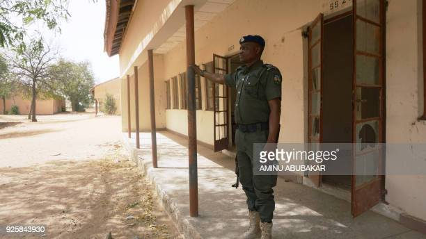 A policeman stands on guard at the premises of Government Girls Technical College where 110 girls were kidnapped by Boko Haram Islamists at Dapchi...