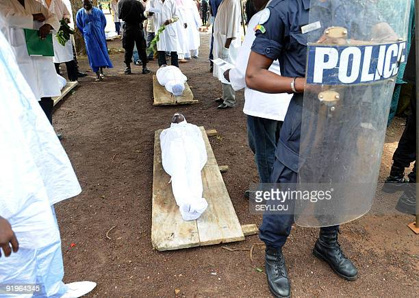 A policeman stands on October 2 2009 next to the bodies of people shot dead by Guinea junta forces on September 28 2009 in front of the Conakry great...