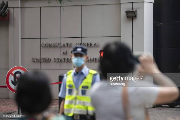 Policeman stands on the street in front of the U.S. Consulate General Chengdu as onlookers snap pictures with their phones in Chengdu, China, on...