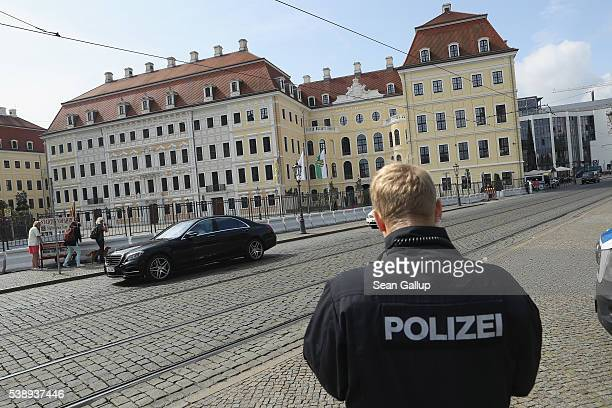A policeman stands outside the Hotel Taschenbergpalais Kempinski Dresden as a limousine drives past on June 9 2016 in Dresden Germany The...