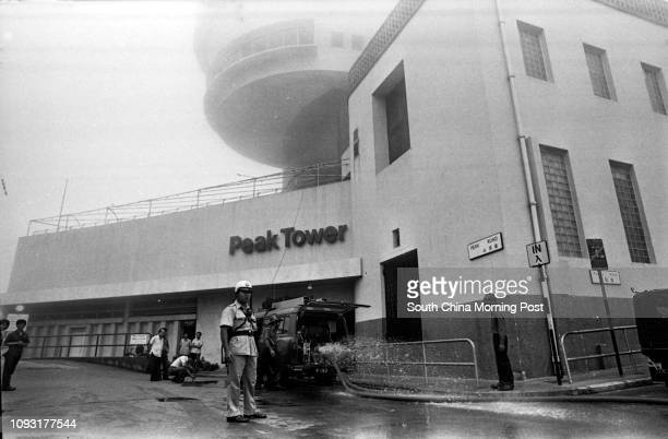 A policeman stands outside the Peak Tower where a fire had just been put out Fire swept the kitchen of the Lo Fung Peak Restaurant in the Tower when...