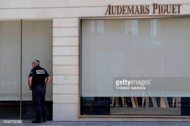 Policeman stands outside the the Swiss watchmaker Audemars Piguet shop on August 18, 2018 in Paris following a robbery. - Two armed men robbed the...
