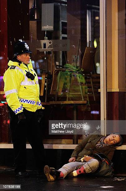 A policeman stands over an unconscious woman after New Years Eve festivities on January 1 2011 in Newcastle United Kingdom Newcastle has a reputation...