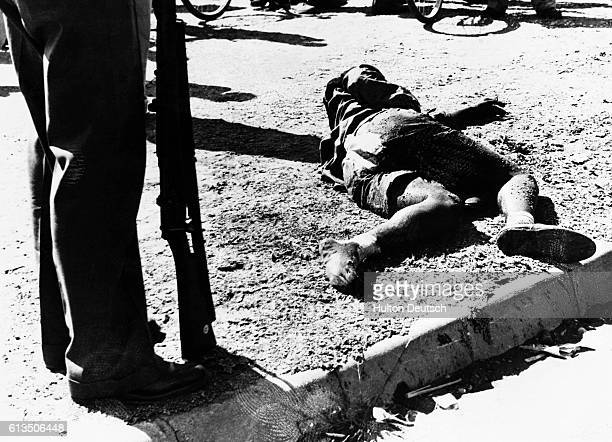 A policeman stands over the corpse of a South African killed by police during a demonstration at Sharpeville