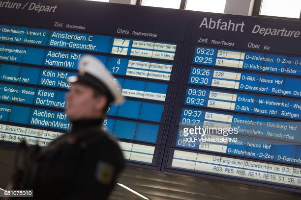 A policeman stands under a schedule board on March 10 2017 in Duesseldorf western Germany one day after German police have arrested an axewielding...