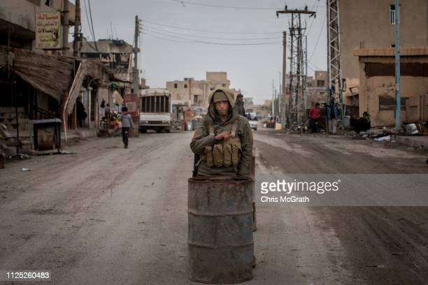 A policeman stands watch at a check point on February 16 2019 in Hajin Syria Civilians have begun returning to some small towns close to Bagouz that...