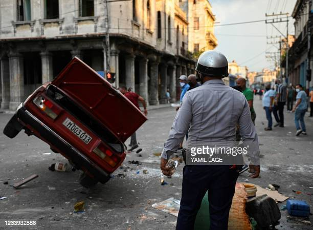 Policeman stands while watching a police car overturned in the street in the framework of a demonstration against Cuban President Miguel Diaz-Canel...